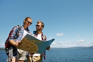 Reisende am Meer mit Karte